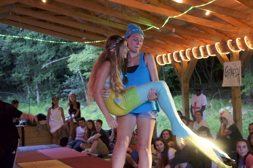 Girl dressed as a mermaid being carried by another camper on stage