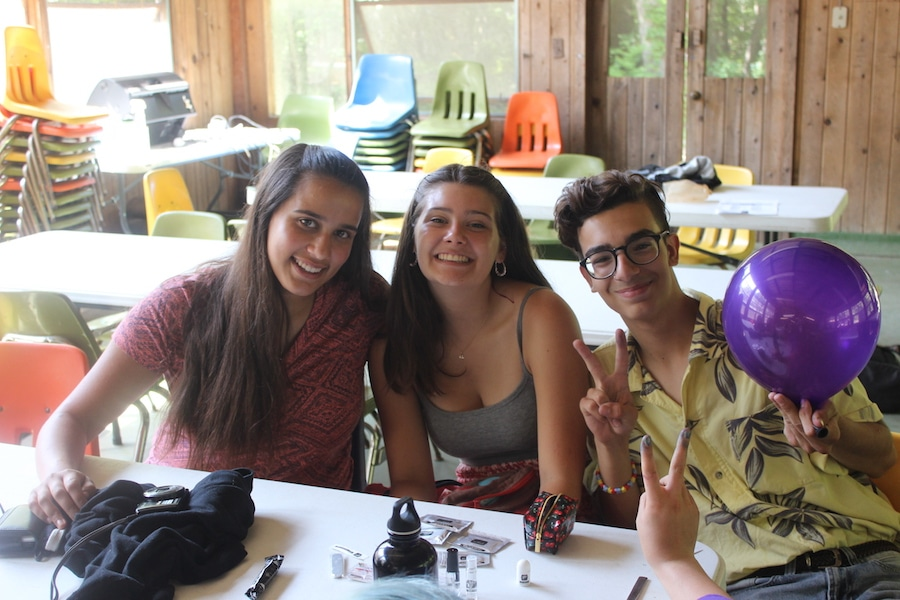 Three campers sitting at a table in the dining hall, smiling and flashing peace signs