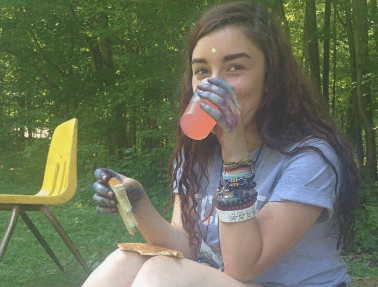Gemma drinking a juice sitting outside the Dining Hall
