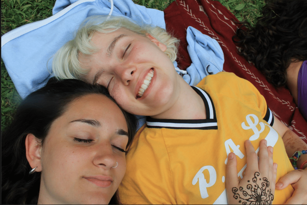 Two girl campers lying down on a blanket