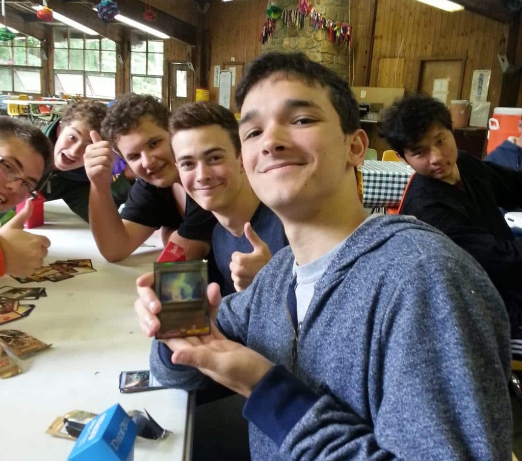 6 young men at Odyssey Teen Camp showing off a rare card from a booster pack at Odyssey Teen Camp.